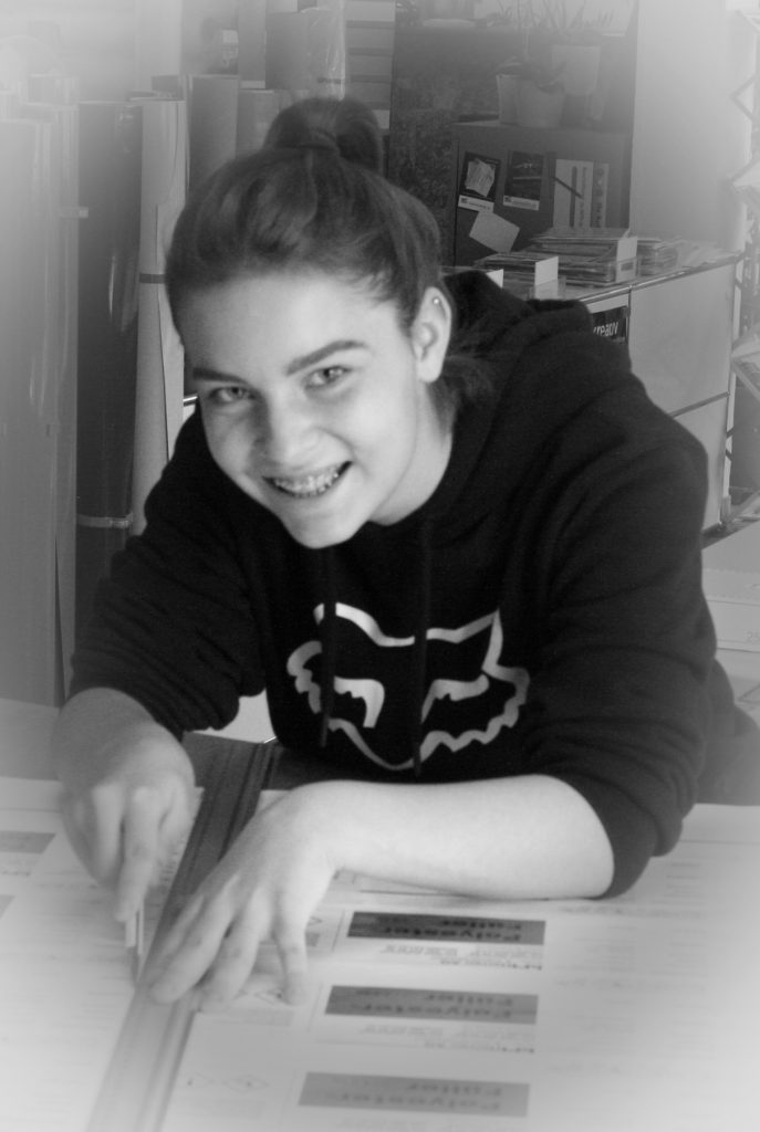 Lorena in ihrer ersten Arbeitswoche beim Zuschneiden von Aufklebern